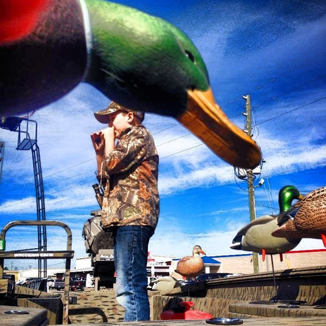 Kid blowing a duck call at Schofield's Hardware Waterfowl Day